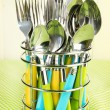 Knives, forks and spoons in metal stand on tablecloth on beige background — Stock Photo #49554069