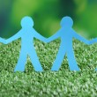 Paper people on green grass, close up — Stock Photo #49555869