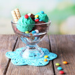 Chocolate ice cream with multicolor candies and wafer rolls in glass bowl, on color wooden table, on bright background — Stock Photo #49556495