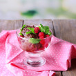 Chocolate ice cream with mint leaf and ripe berries in glass bowl, on wooden table, on bright background — Stock Photo #49556565