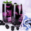 Tasty cool blackberry lemonade with ice on wooden table, on light background — Stock Photo #49557915
