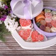 Present box with sweets and flowers on wooden background — Stock Photo #49558331