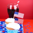 American patriotic holiday cupcakes and glass of cola on red background — Stock Photo #49559139