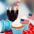 American patriotic holiday cupcakes and glass of cola on wooden table — Stock Photo #49559171