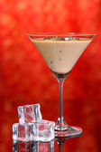 Baileys liqueur in glass on red background — Stock Photo