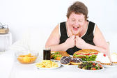 Fat man has a big lunch, on home interior background   — Stock Photo
