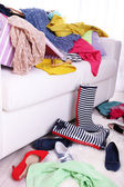 Messy colorful clothing on  sofa on light background — Zdjęcie stockowe