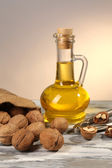 Walnut oil and nuts on wooden table — Stock Photo