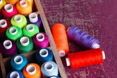 Multicolor sewing thread in wooden box, on wooden background, close-up — Stok fotoğraf