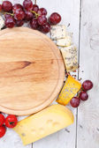 Different types of cheese with empty board on table close-up — Stockfoto