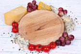 Different types of cheese with empty board on table close-up — Zdjęcie stockowe