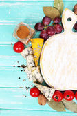 Different types of cheese with empty board on table close-up — ストック写真