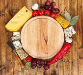 Different types of cheese with empty board on table close-up — Stok fotoğraf
