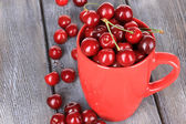 Sweet cherries in mug on wooden background — Stock Photo