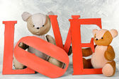 Decorative letters forming word LOVE with teddy bear on grey background — Stock Photo
