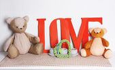 Decorative letters forming word LOVE with teddy bear on wall background — Stock Photo