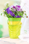 Bouquet of colorful flowers in decorative bucket, on chair, on bright background — Stock Photo