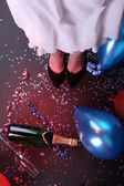 Legs with confetti, champagne and balloons on the floor — Zdjęcie stockowe