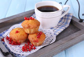 Tasty muffin with red currant berries on tray, on color wooden background — Stock Photo