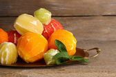 Citrus fruits without skin on tray, on wooden background — Stock Photo