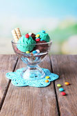 Chocolate ice cream with multicolor candies and wafer rolls in glass bowl, on color wooden table, on bright background — Stock Photo