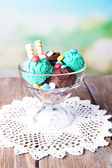 Chocolate ice cream with multicolor candies and wafer rolls in glass bowl, on color wooden table, on bright background — Stok fotoğraf