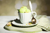 Tasty pistachio ice cream in cup on wooden table, on light background — Stok fotoğraf