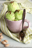 Tasty pistachio ice cream in cup on wooden table — Stock Photo