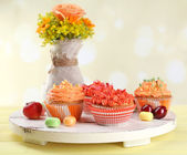 Tasty cupcakes on table, on bright background — Stock Photo