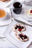 Fresh bread with cherry jam and homemade butter on plate on wooden background — Zdjęcie stockowe