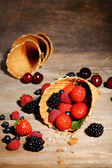 Different ripe berries in sugar cone, on wooden background — 图库照片