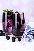 Tasty cool blackberry lemonade with ice on wooden table, on light background — Stock Photo