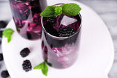 Tasty cool blackberry lemonade with ice on wooden table — Stock Photo