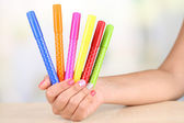Female hand with stylish colorful nails holding felt pens, on wooden table, on bright background — Stock Photo