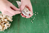 Hand with tweezers holding pearl and oyster on wooden background — Stok fotoğraf