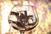 Glass with ice cubes on color background — Stock Photo