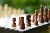 Chess board with chess pieces on bright background — Stock Photo