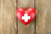 Red heart with cross sign on wooden background — Stock Photo