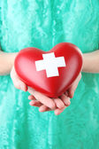Red heart with cross sign in female hand, close-up,  — Foto de Stock