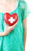 Red heart with cross sign in female hand, close-up, isolated on white — Stockfoto