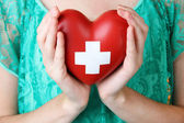 Red heart with cross sign in female hand, close-up, on color background — Foto de Stock