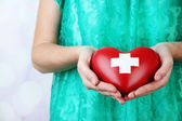 Red heart with cross sign in female hand, close-up, on light background — Foto Stock