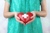 Red heart with cross sign in female hand, close-up, on light background — Stock fotografie