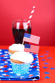 American patriotic holiday cupcakes and glass of cola on red background — Stock Photo
