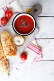 Homemade tomato juice in color mug, bread sticks, spices and fresh tomatoes on wooden background — Stock Photo