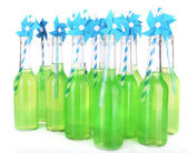 Bottles of drink with straw on light background — Stock Photo