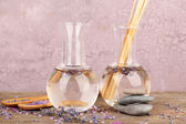 Spa still life with lavender oil and flowers on wooden table, on pink background — Stock Photo