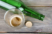 Bottle and glass with cold drink, on wooden background — Стоковое фото