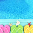 Colored flip flops on wooden platform beside sea — Stock Photo #49762025