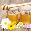 Jar full of delicious fresh honey and wild flowers on wooden table — Stock Photo #49765313